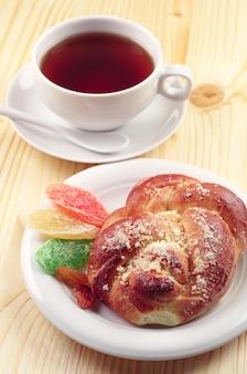 木製のテーブルにドライフルーツと甘いパンとお茶のカップ