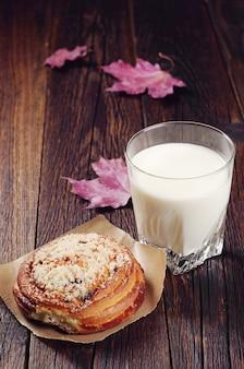Сладкая булочка и стакан молока на старом деревянном столе