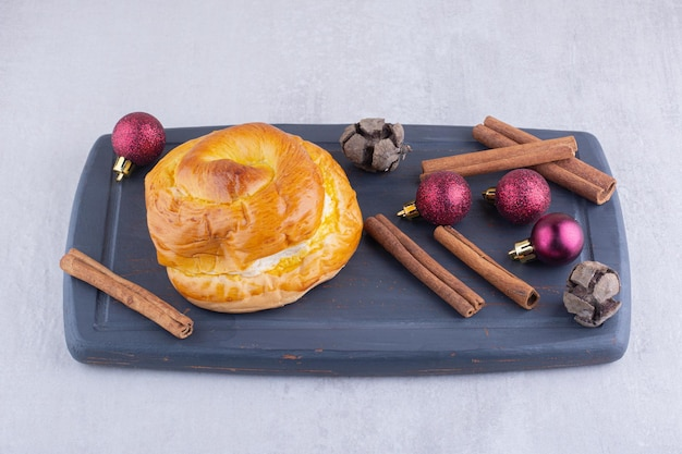 Sweet bun, cinnamon sticks and christmas decorations on a wooden platter on white surface