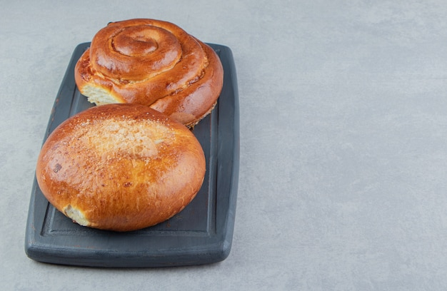 Sweet bun pastries on black board.