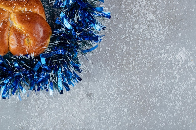 Sweet bun in a ring of tinsel on marble table.
