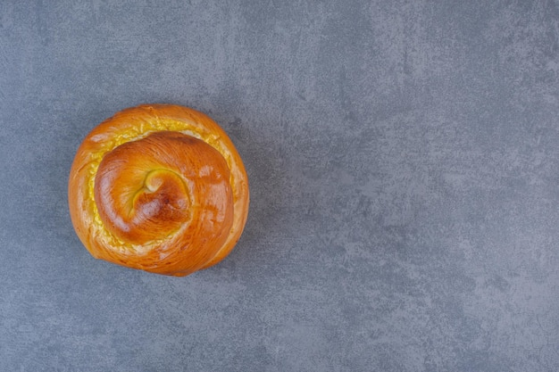 Sweet bun standing upright on marble background. high quality photo