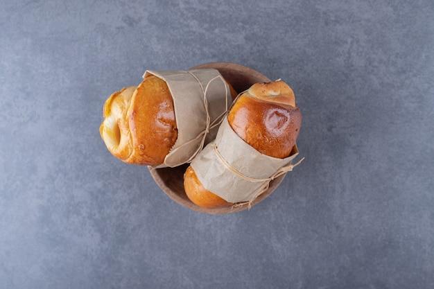 大理石の上に、ボウルの糸で結ばれた甘いパン。