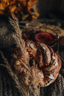 Sweet bun with almonds lying on a knitted fabric with autumn dried flowers. cozy home still life