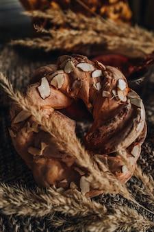 アーモンドが秋のドライフラワーのニット生地の上に横たわっている甘いパン。居心地の良い家の静物