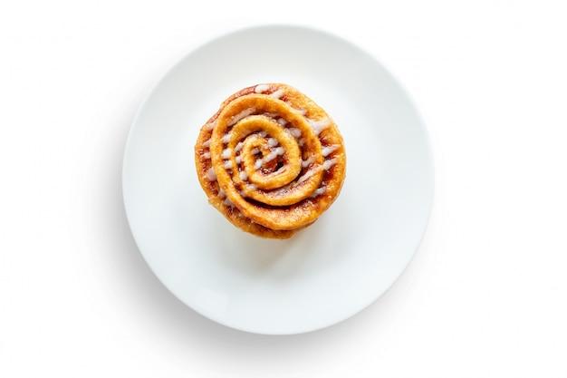Сладкая булочка с булочкой с корицей положить на белую тарелку, изолированную на белом фоне.