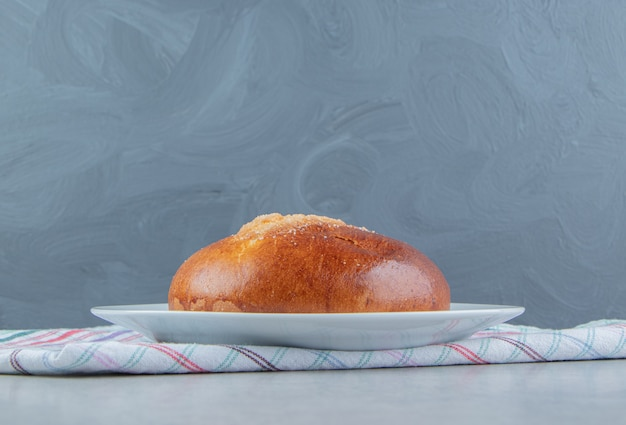 Сладкая булочка с тканью на белой тарелке.