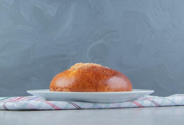 Panino dolce con panno sul piatto bianco.