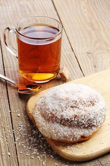 ココナッツチップスと熱いお茶のガラスカップと甘いパン