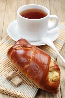 テーブルの上にカッテージチーズとお茶の甘いパン