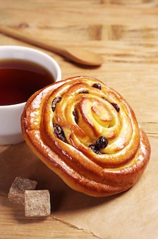 Sweet bun with cup of tea on old wooden background