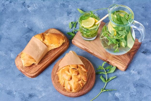 Сладкая булочка с мохито на деревянной доске на синем