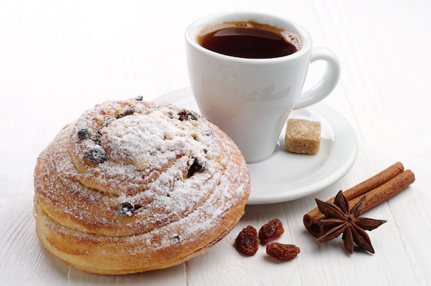 Sweet bun with raisins and cup of coffee on white table