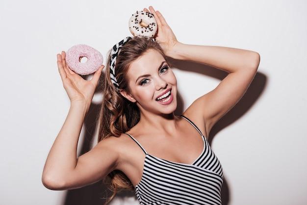 달콤한 토끼. 흰색 배경에 서 있는 동안 머리 위로 도넛을 들고 있는 쾌활한 젊은 여성