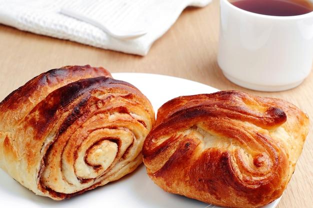 テーブルのクローズアップの甘いパンとカップティー