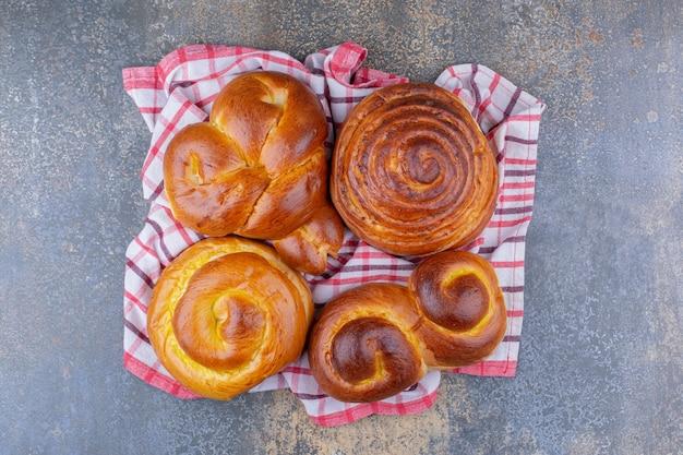 大理石の表面のしわのあるタオルに束ねられた甘いパン