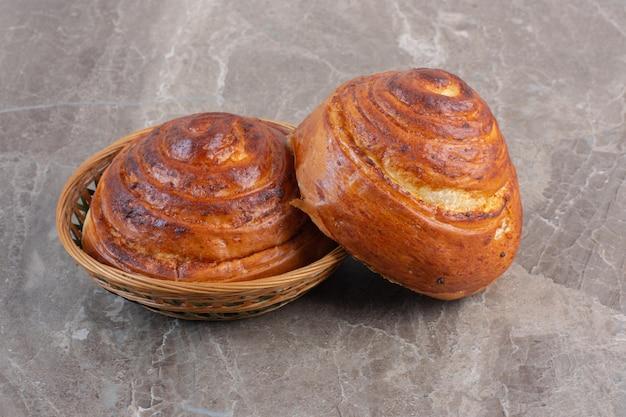 Сладкие булочки внутри и прислонившись к маленькой корзинке на мраморном фоне. фото высокого качества