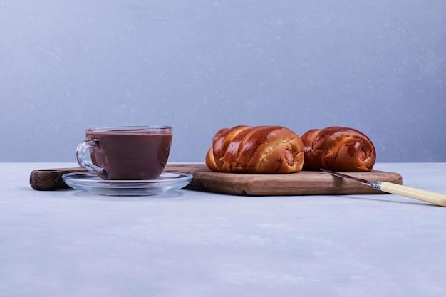 青い背景にお茶と甘いパン。高品質の写真