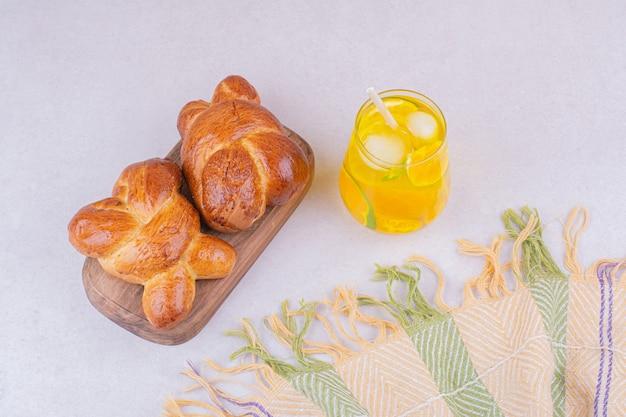 レモンジュースのグラスと甘いパン