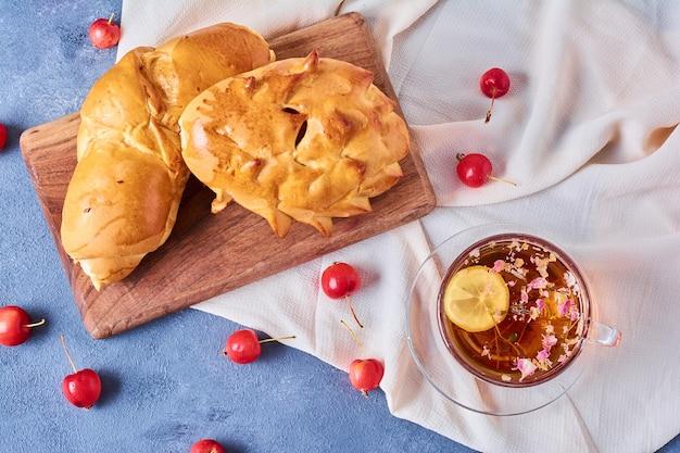 青の木板にハーブティーと甘いパン