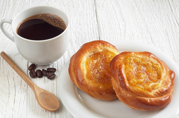 ジャムとホットコーヒーのカップと甘いパン