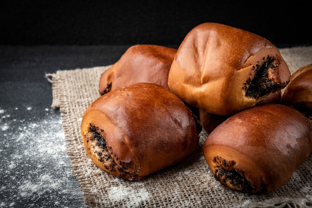 Sweet buns with poppy seeds on dark background.