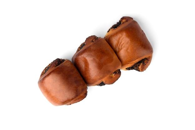 白い背景で隔離のケシの実と甘いパン。上面図。