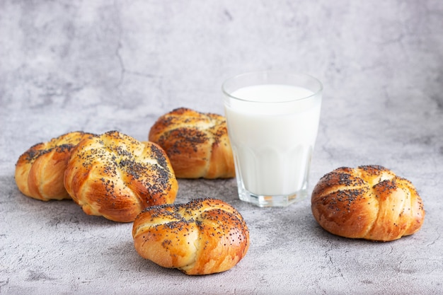 Sweet buns with poppy seeds served with milk. selective focus.
