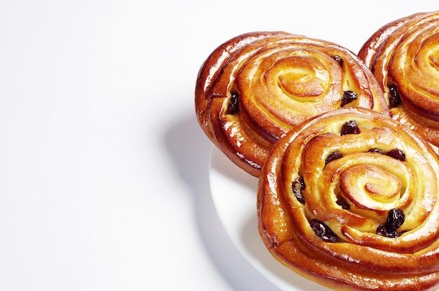Sweet buns with raisins on white background
