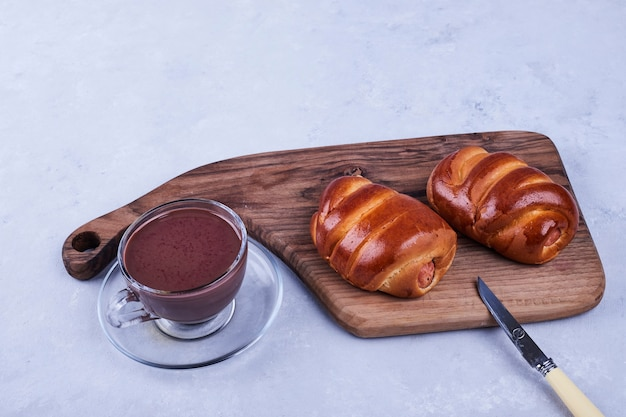 Sweet buns on a wooden board with a cup of hot chocolate on blue