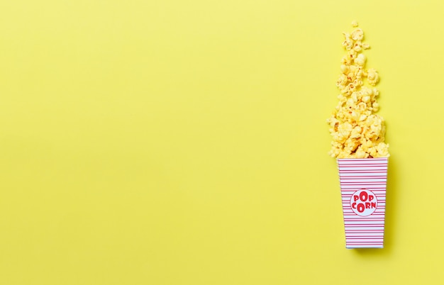 Sweet butter popcorn in box on  yellow background