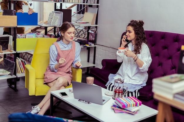 甘いカカオドリンク。書店の寒いエリアに座ってノートパソコンで情報を観察するファッショナブルな格好良い女性