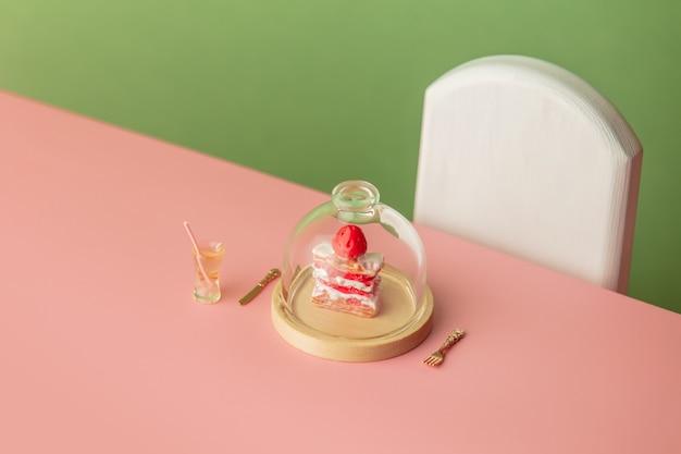 분홍색 테이블과 녹색 배경에 달콤한 케이크와 음료