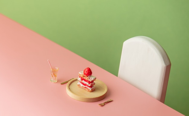 Sweet cake and drink on pink table and green background