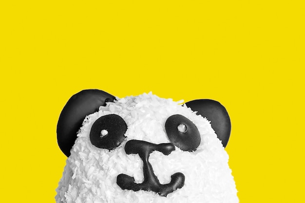 Sweet cake in the form of a panda head. eyes, ears and nose made of dark chocolate. sprinkled with coconut chips. isolated on yellow backgroud