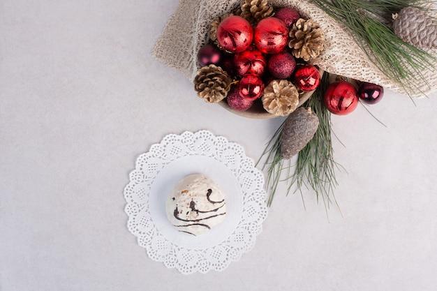 皿の上の甘いケーキと白い表面のクリスマスのおもちゃ
