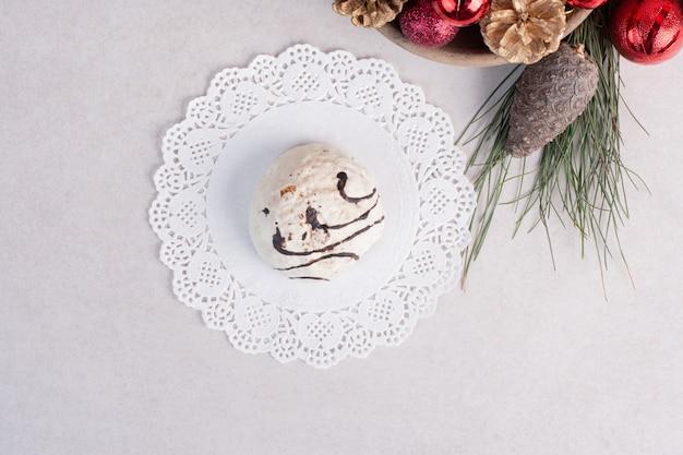 Сладкий торт на тарелке и елочные игрушки на белой поверхности