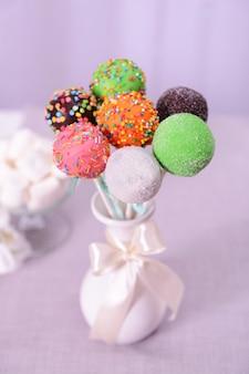 밝은 배경에 테이블에 꽃병에 달콤한 케이크 팝