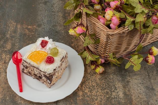 大理石の表面にバラのバスケットと甘いケーキ