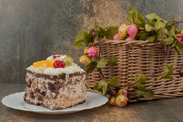 Torta dolce con cesto di rose sul tavolo di marmo