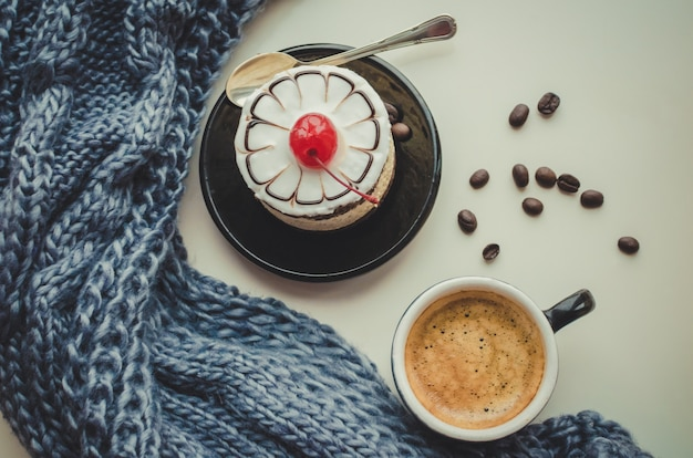 Sweet cake with a cherry and cup of coffee