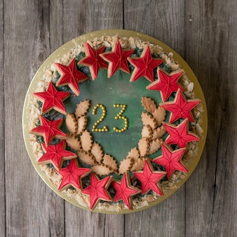 Sweet cake with decor on 23 february holiday on light wooden background