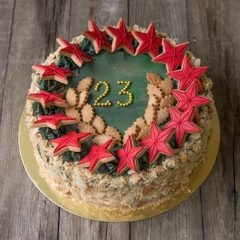 明るい木製の背景に2月23日の休日の装飾が施された甘いケーキ