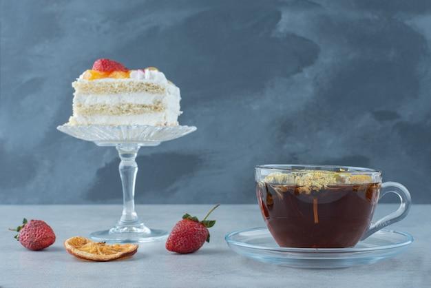 大理石の背景にドライオレンジとハーブティーのカップと甘いケーキ。高品質の写真