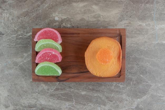 나무 접시에 마멀레이드 사탕과 달콤한 케이크