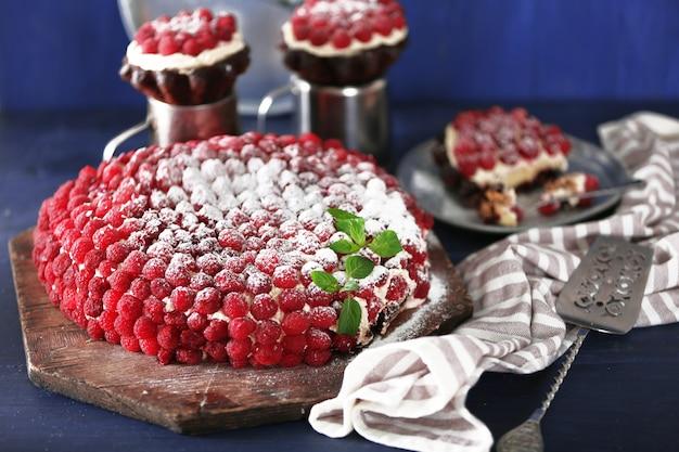 色の木製のテーブルにラズベリーの甘いケーキ