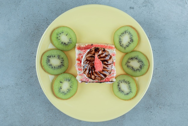 Sweet cake with slices of kiwi on a green plate .