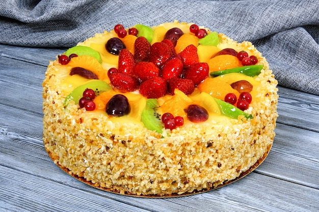 Sweet cake with strawberries on grey wooden background.