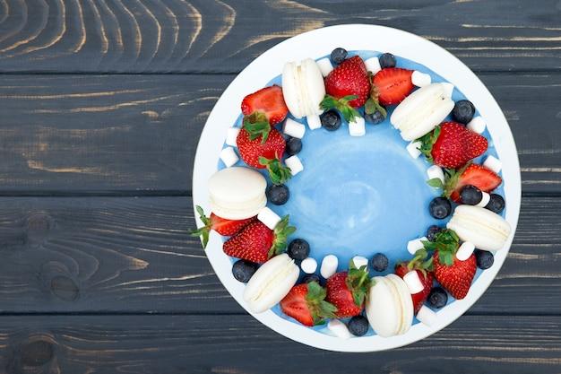 灰色の木製の背景の上のプレートにイチゴと甘いケーキ