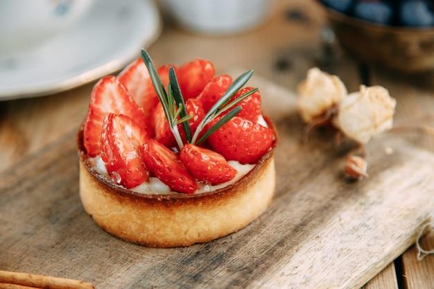 나무 테이블 근접 촬영에 딸기와 달콤한 케이크 효모가없는 반죽으로 만든 케이크